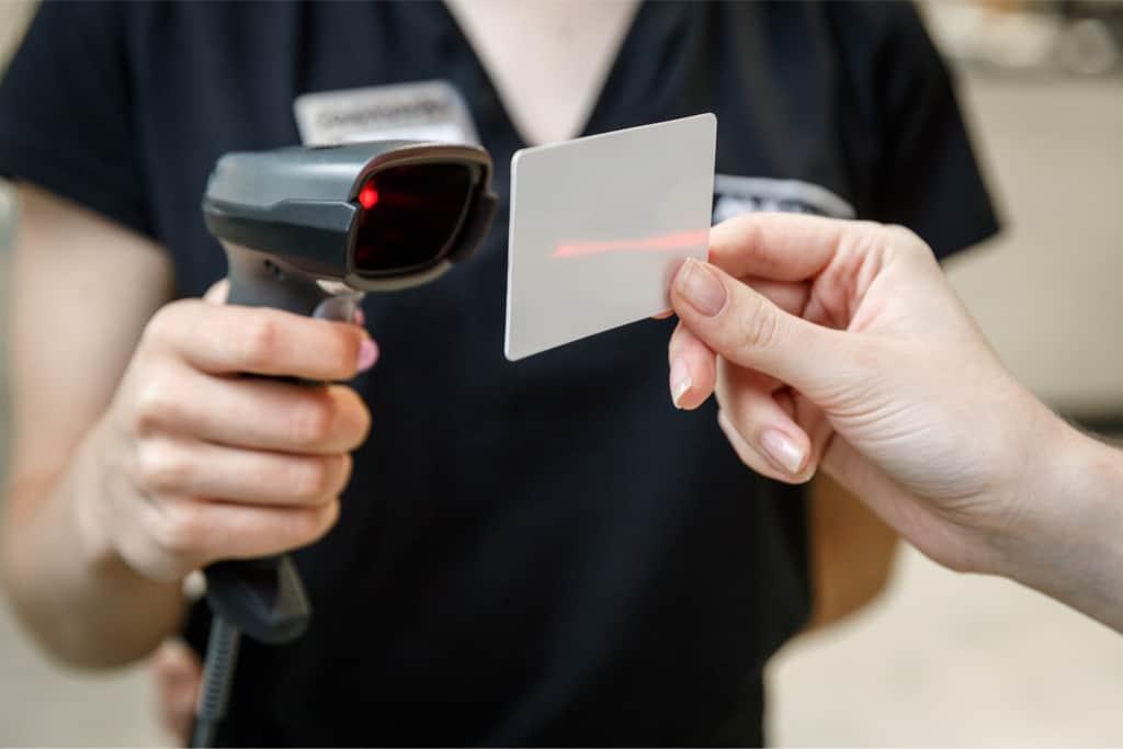 Sprzedawca, trzymający w ręku czytnik kodów kreskowych, sczytujący kod z karty stałego klienta uczestnika programu lojalnościowego Loyalty Starter