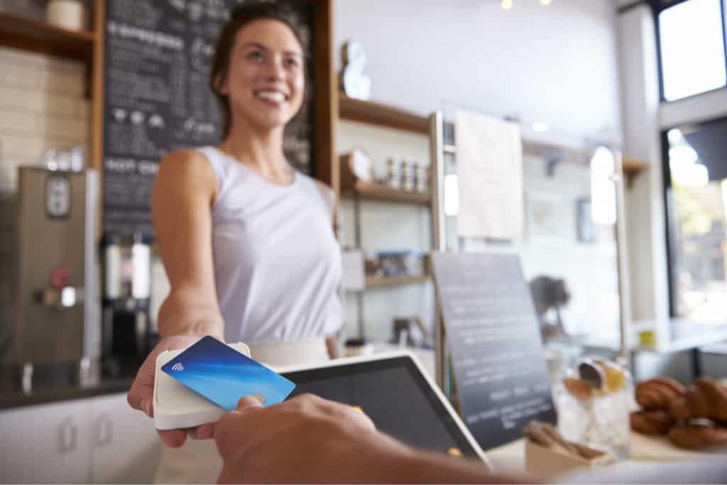 Uczestnik programu lojalnościowego Loyaty Starter przykładający w sklepie do czytnika zbliżeniową kartę stałego klienta