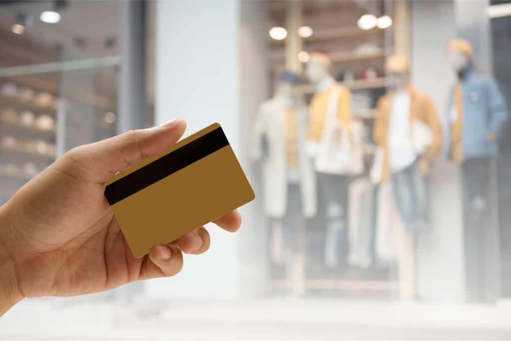 Dłoń uczestnika programu lojalnościowego, trzymająca magnetyczną kartę stałego klienta z paskiem magnetycznym