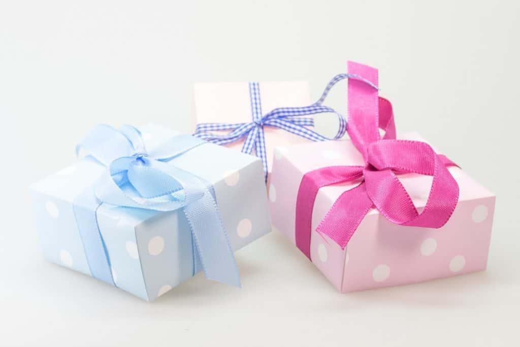 Grafika przedstawiająca trzy prezenty z kokardkami w różnych kolorach.