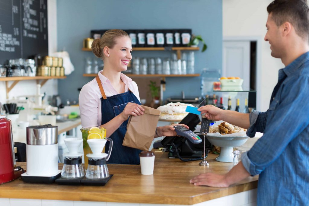 Grafika przedstawiająca klienta obsługiwanego przez ekspedientkę w cukierni.