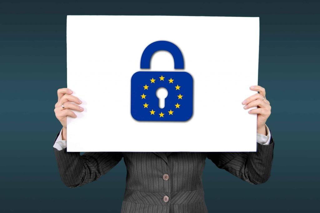 Zdjęcie osoby trzymającej kartkę z symbolem ochrony danych osobowych