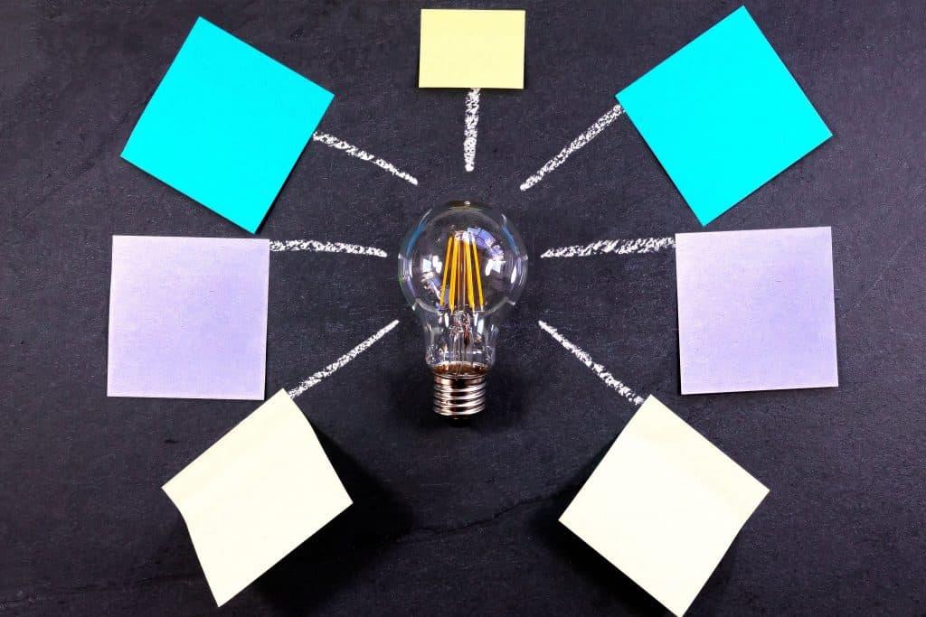 Grafika przedstawiająca żarówkę i dookoła niej karteczki, służące do zapisywania notatek.