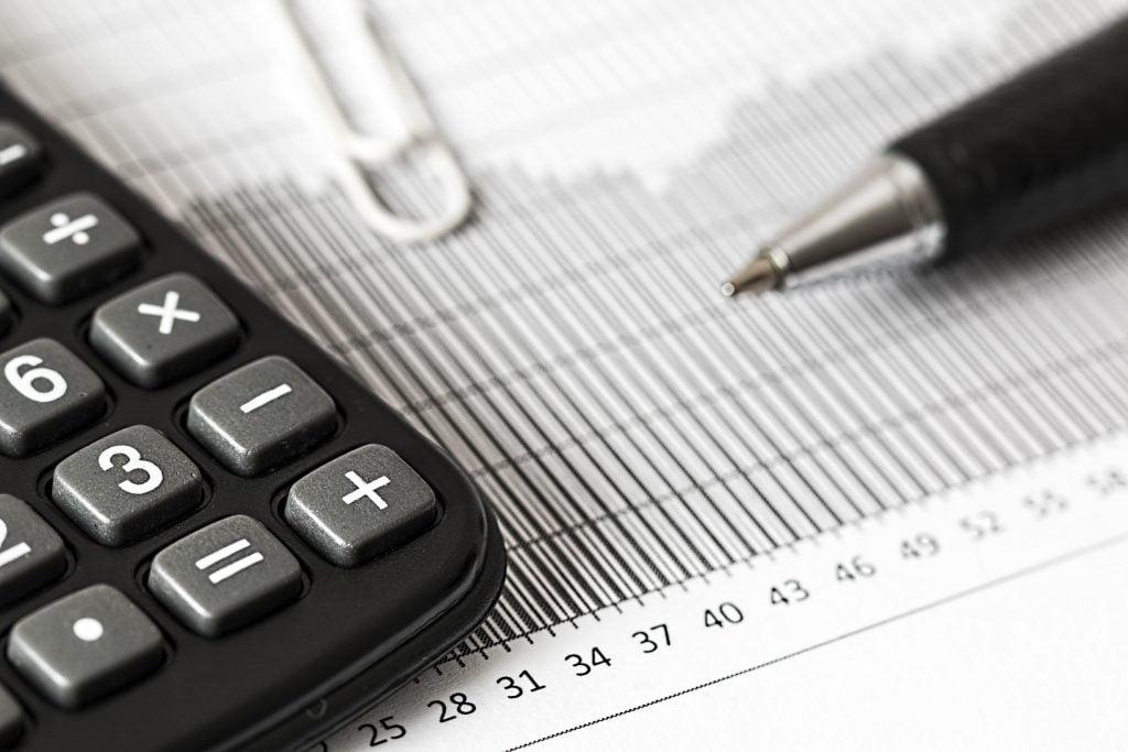 Grafika przedstawiająca kalkulator oraz długopis.