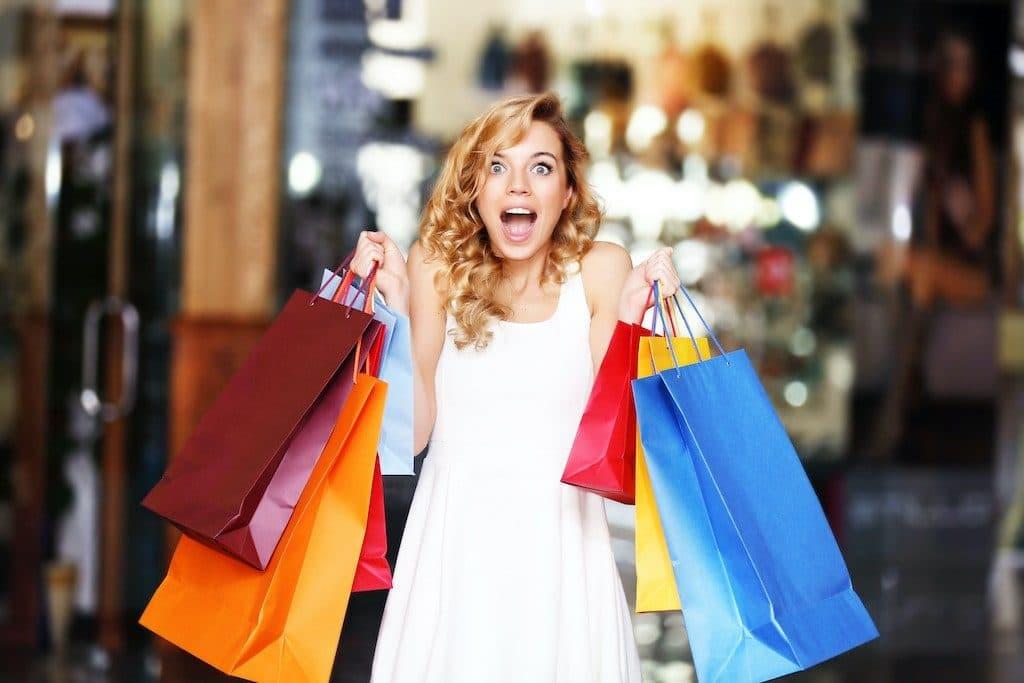 Grafika przedstawiająca kobietę trzymającą kolorowe torby z zakupami.