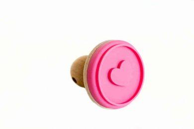 Grafika, przedstawiająca różową pieczątkę z sercem.